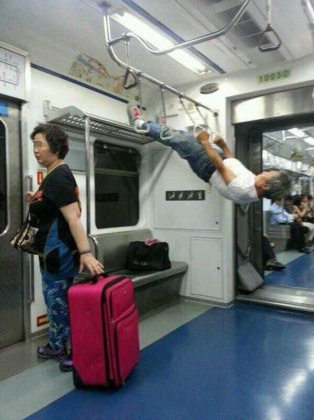 電車内のつり革と網棚を使って筋トレする男性!