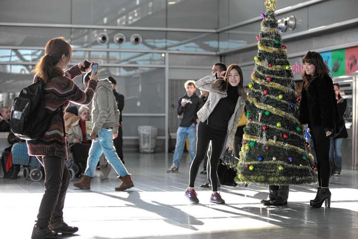 人? フェリーターミナルで人々を喜ばせようとするクリスマスツリー人間(笑)