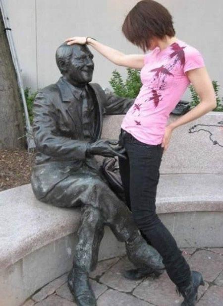 やあ! おもしろいポーズの銅像で遊ぶ女性(笑)