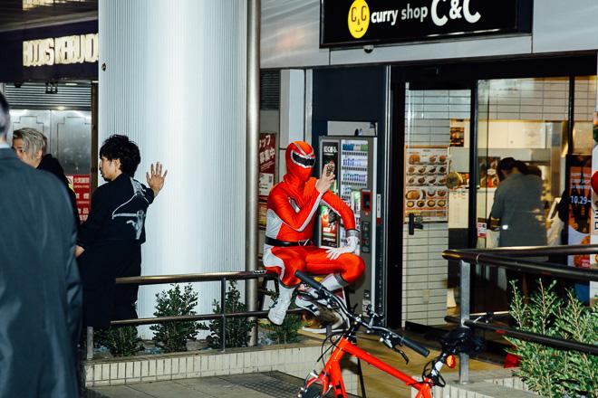 【渋谷ハロウィンおもしろ画像】まだかなー? スマホ見ながら仲間の到着を待つアカレンジャーをハロウィン渋谷で見かける(笑)