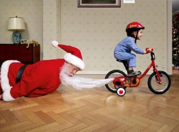 ちょっとストップ! 子どもの三輪車にひげを巻き込まれて引きずられるサンタクロース(笑)