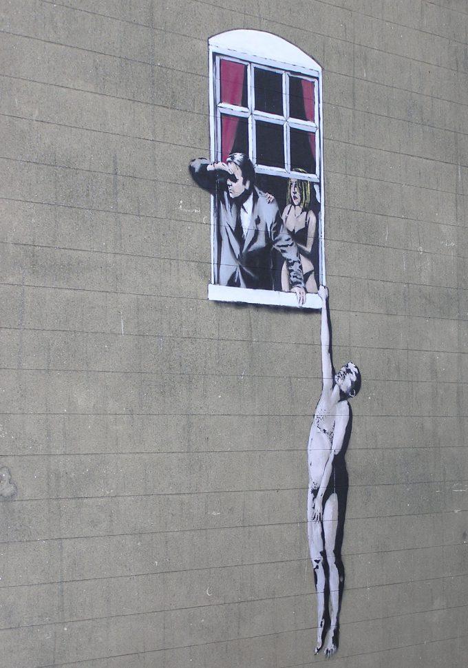 バンクシーの作品バスルームの窓からぶら下がる裸の男