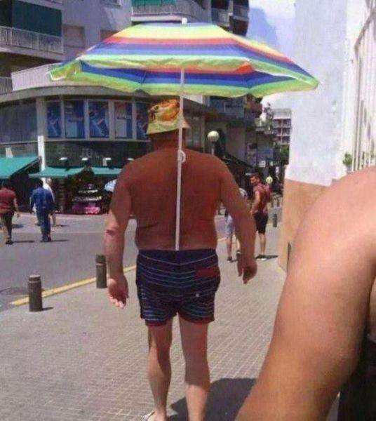 楽! ビーチパラソルをズボンに入れて日傘替わりに使う男性(笑)
