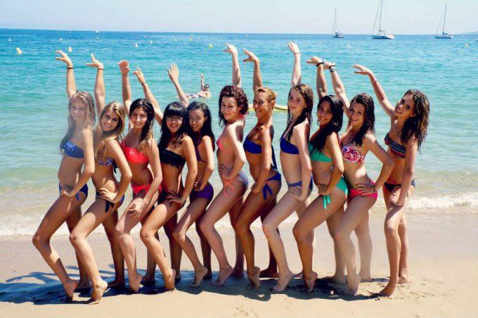 はいチーズ! 海で水着女性たちが記念撮影をしている後ろでちゃっかり写る男性(笑)