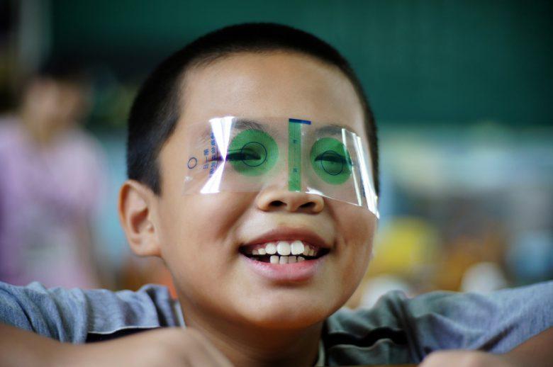 ぎょう虫検査フィルムを目に貼る子ども(笑)