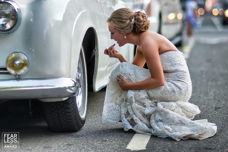 車のタイヤホイールの反射を利用してメイク直しをする花嫁(笑)
