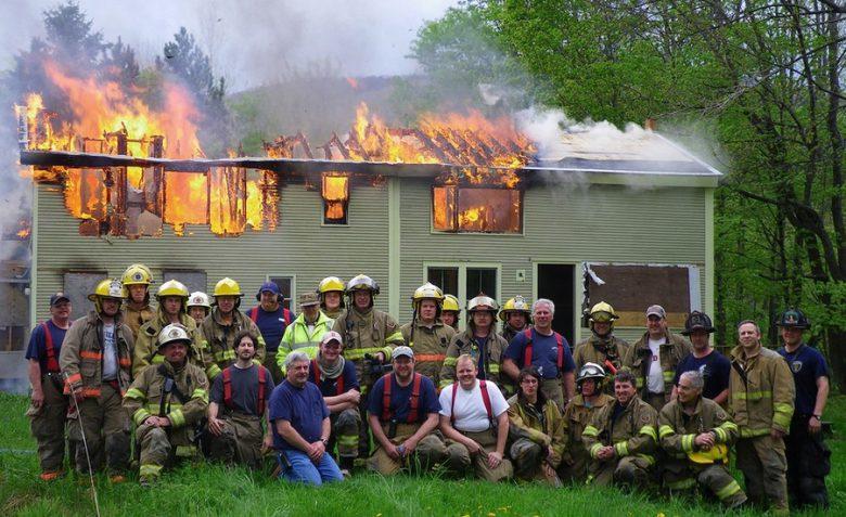 燃えた家の前で記念撮影をする消防隊(笑)
